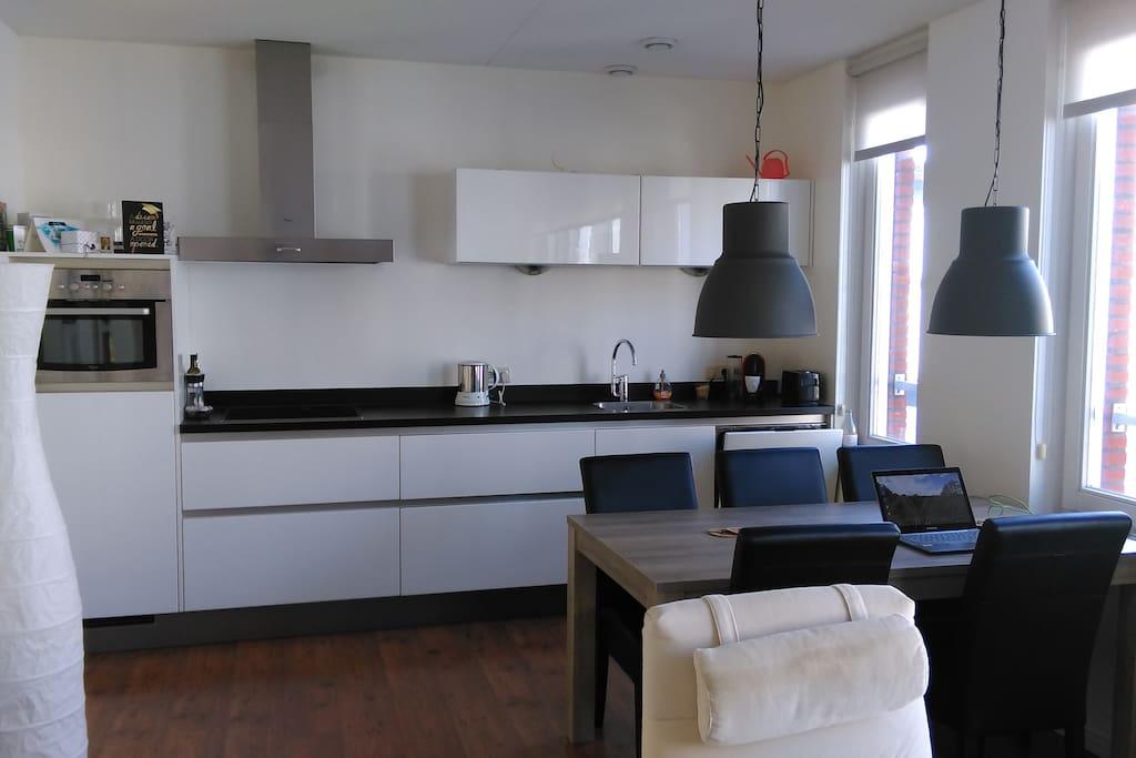 Keuken met kookplaat, elektrische oven/ magnetron, servies en vaatwasser