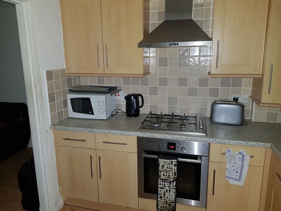 Walk-in kitchen with microwave, kettle cooker and oven, toaster and cupboard space for guests food.