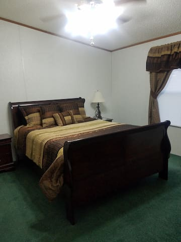 Master bedroom with queen size bed with walk-in closet and attached master bathroom with garden tub.