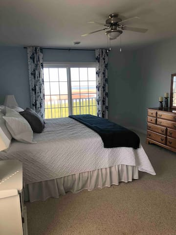 Master bedroom with king sized bed and patio access to the covered porch.