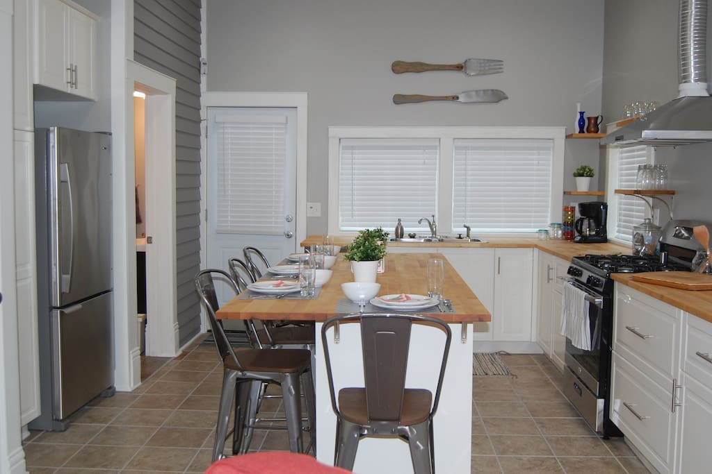 Full kitchen, including cookware, coffee maker, refrigerator and dishwasher, along with an eat-in island