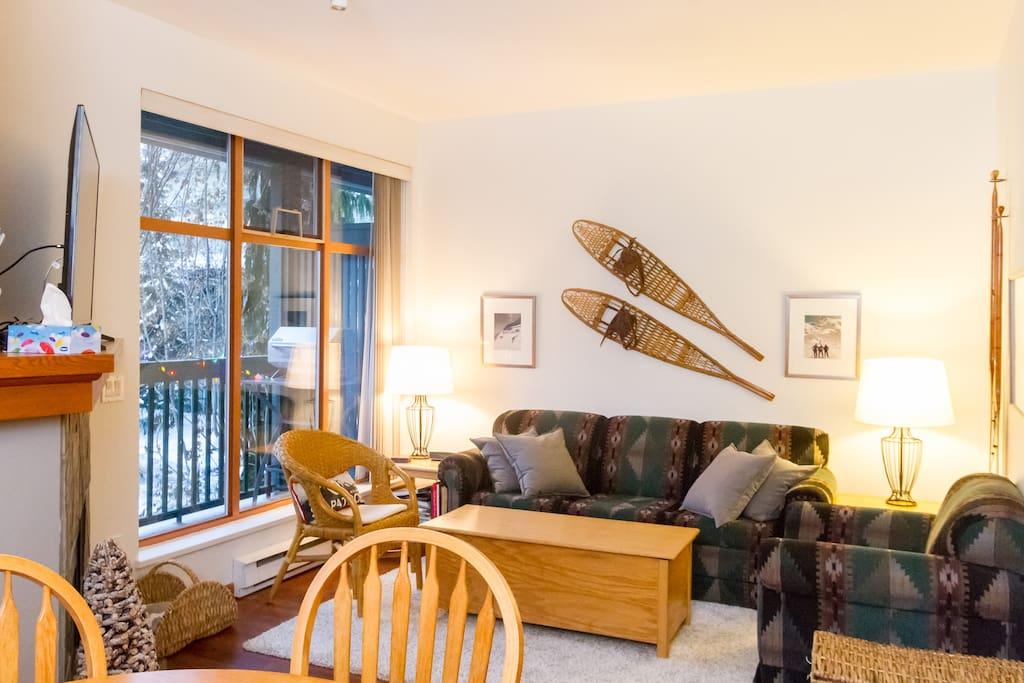 Living room with pull-out couch, fireplace, games, toy box, and views of Whistler