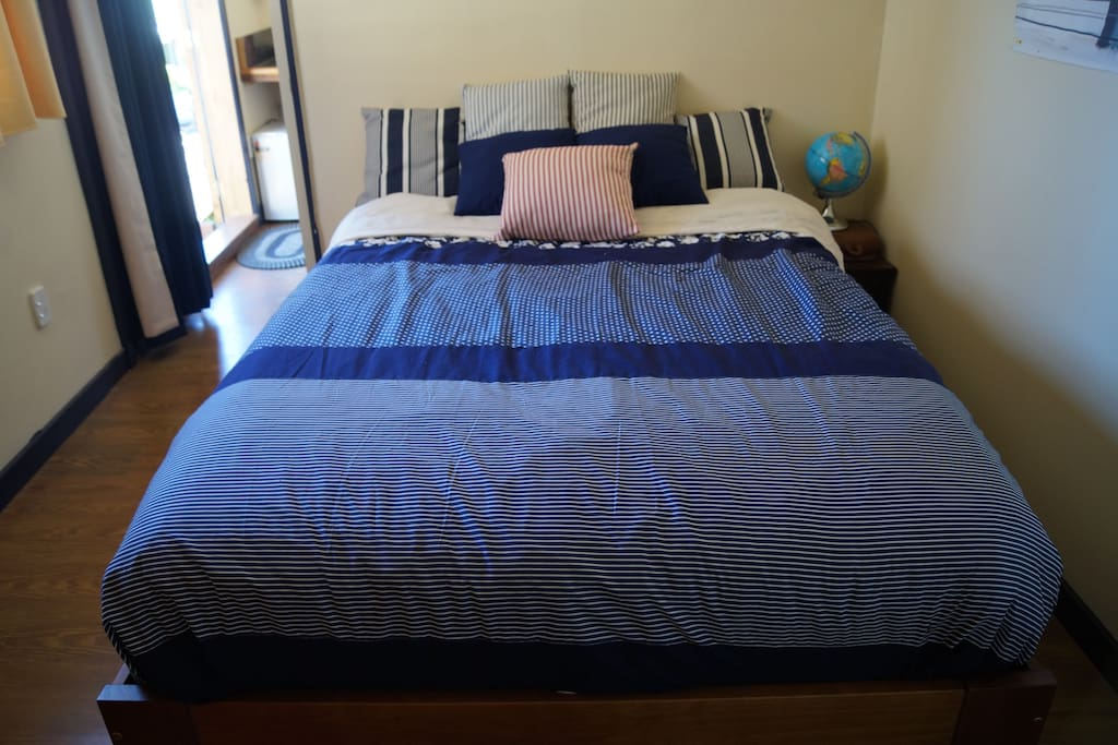 Bedroom with one queen size bed with fresh quality sheeting down duvet and hotel quality towels