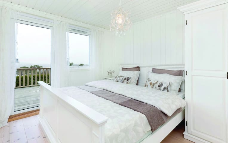 Master bedroom with queen size bed, and chandalier offering views over the Skogsoy archipelago and North Sea, and private door to deck and outdoor entertaining area.