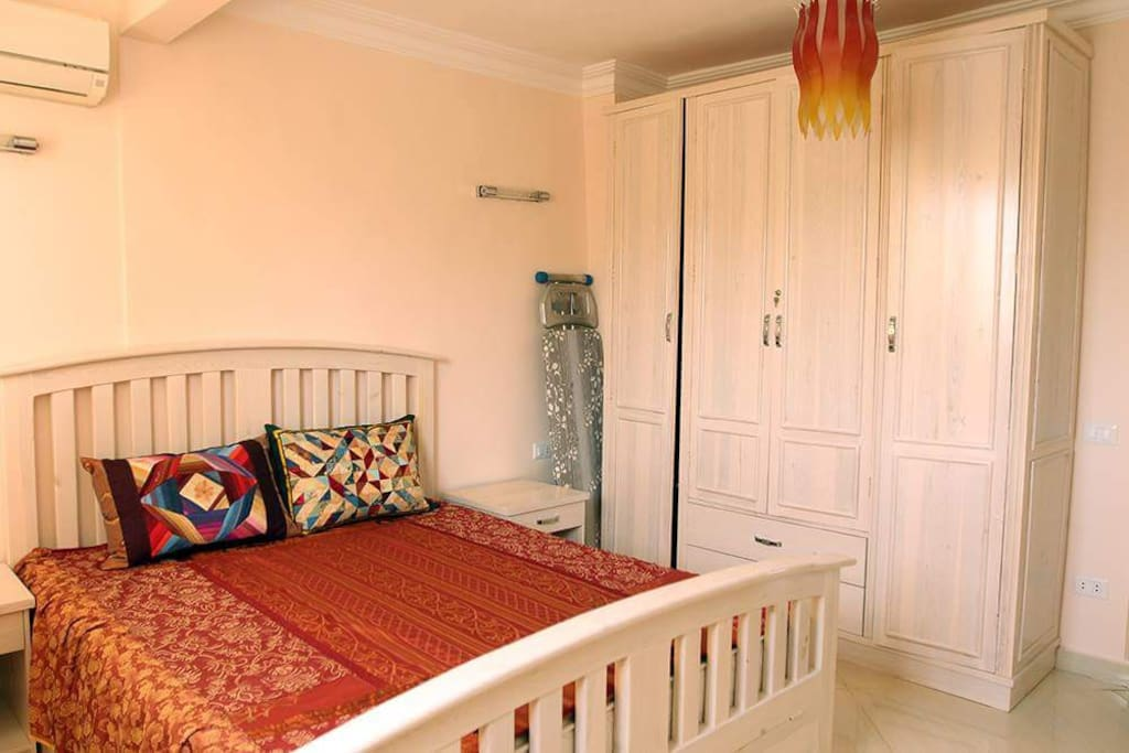 A master bedroom with a king size bed with a new mattress and a big closet. All bedrooms are quipped with quiet airconditioners.