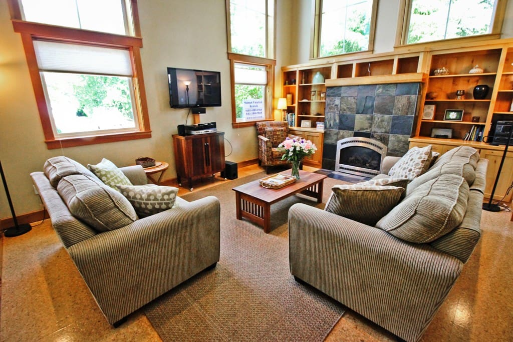 Lower entry level living room with wall mounted flat screen cable TV/DVD, gas fireplace, couch, loveseat, 3-disc CD player and vaulted ceilings.