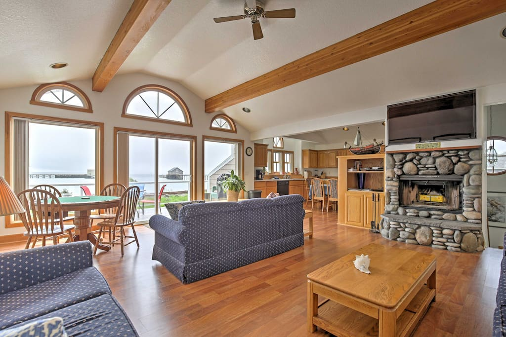 Step inside to find an open living space with a rock fireplace, vaulted ceilings, large windows, and sliding doors leading out to the spacious deck.