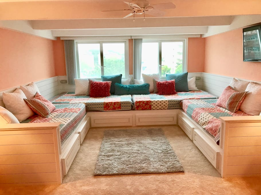 Custom built platform w 2 queens & 2 twin XLs.  This room now serves as an additional family room for the kids.