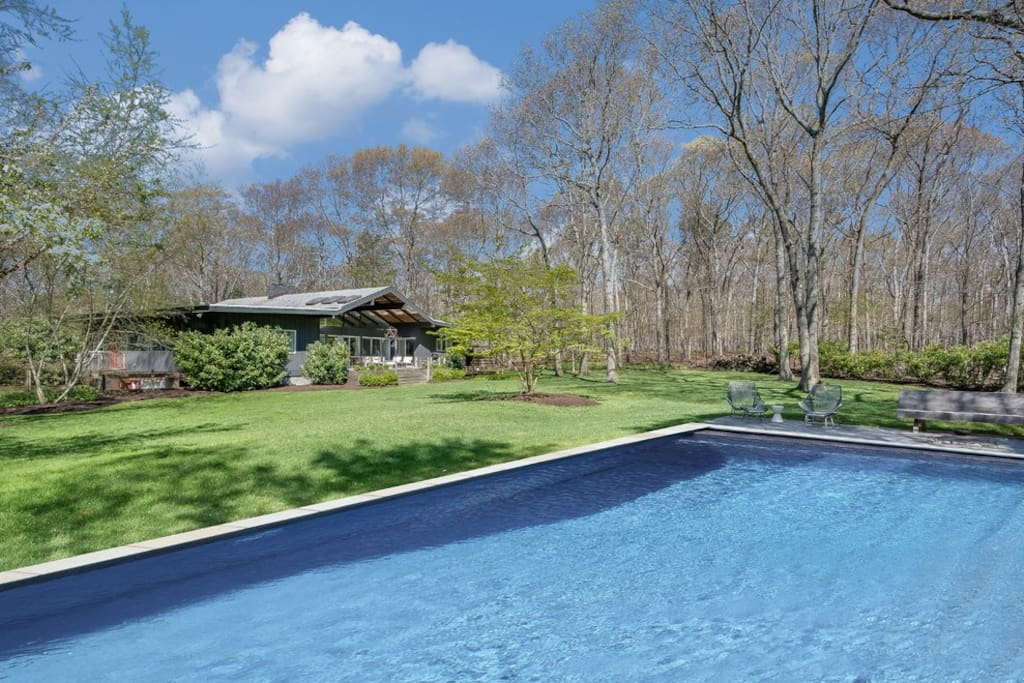 pool with lounge seating and fire pit