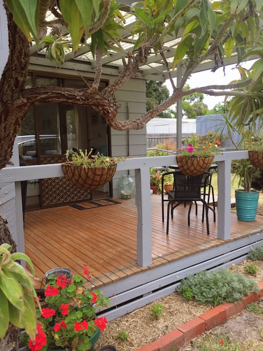 The deck has a separate and intimate setting to enjoy, surrounded by birds and a lush garden