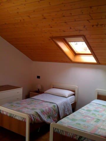 Camera due letti singoli con porta finestra sul poggiolo lato est - vista Valle di Sole