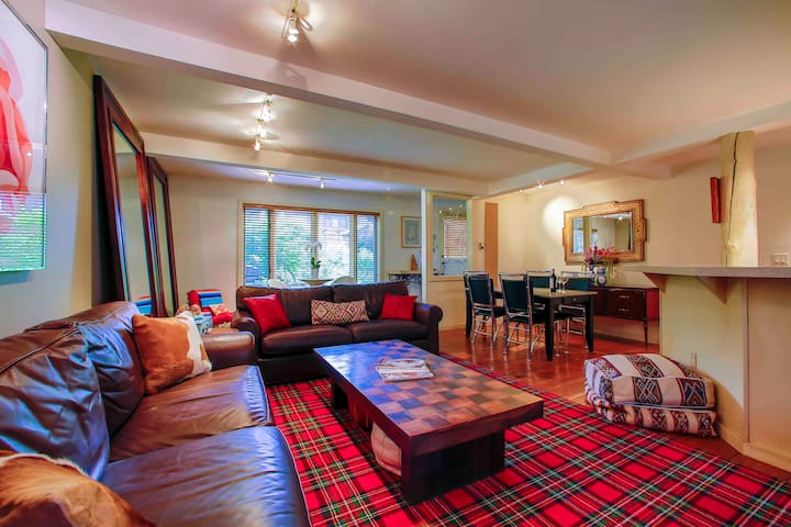 Gorgeous and comfy living room, Italian coach leather couches, Ralph Lauren custom plaid rug, record player, gas modern fire place, flat scream TV , Moroccan poofs and more