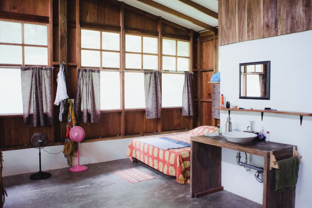 Your cozy, rustic, and eco-friendly room features your own en-suite bathroom, a queen bed and two single beds as well as your own private entrance and standing fans.