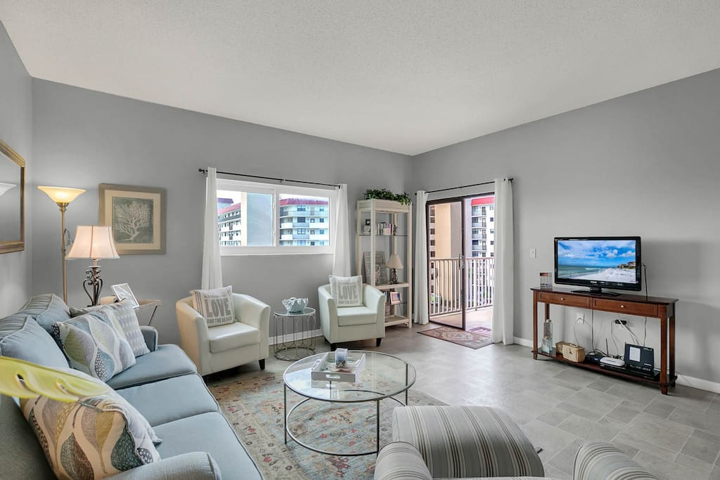 The spacious living room features seating for 6 and access to the private balcony.