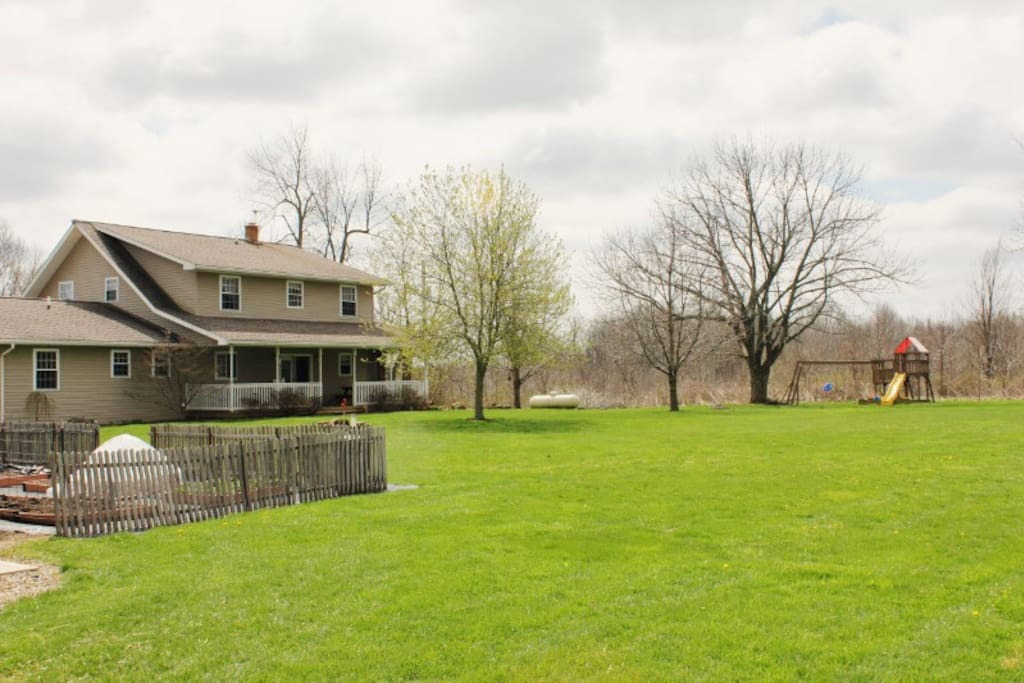 The spacious back yard includes the gardens, swing set and sandbox.