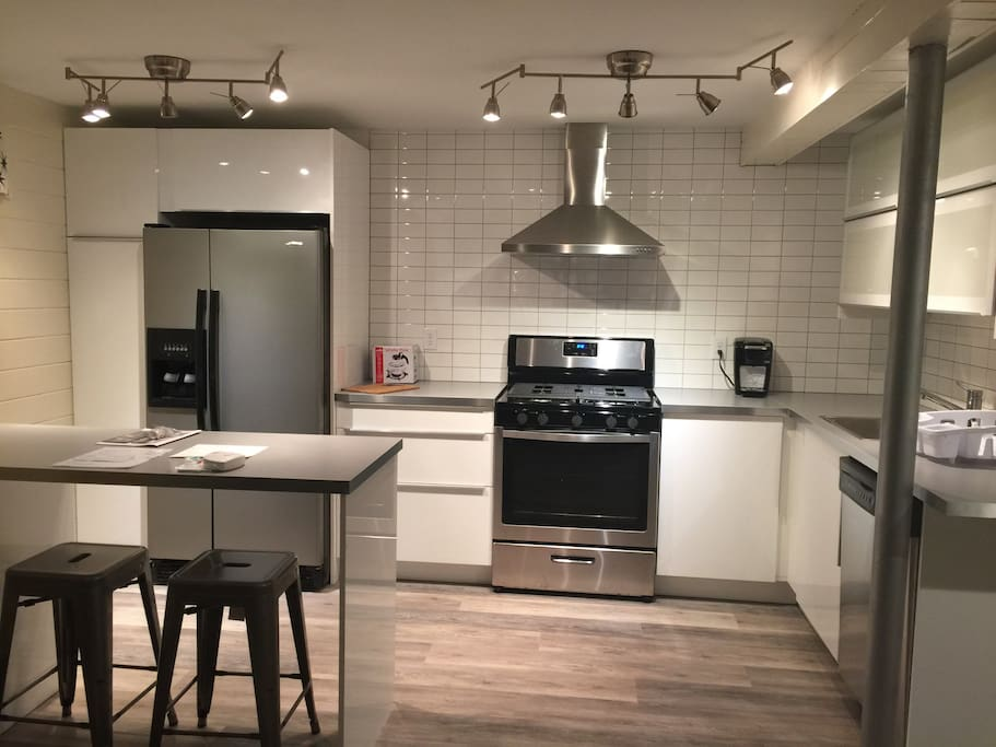 This kitchen is brand new! Stainless appliances that include a dishwasher. Beautiful tile walls/backsplash, new wood look floor. Island for dining or to set up your workspace.