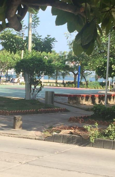 atravesando la calle se encuentra este parque que cuenta con juegos para niños, bancas y cancha de basket