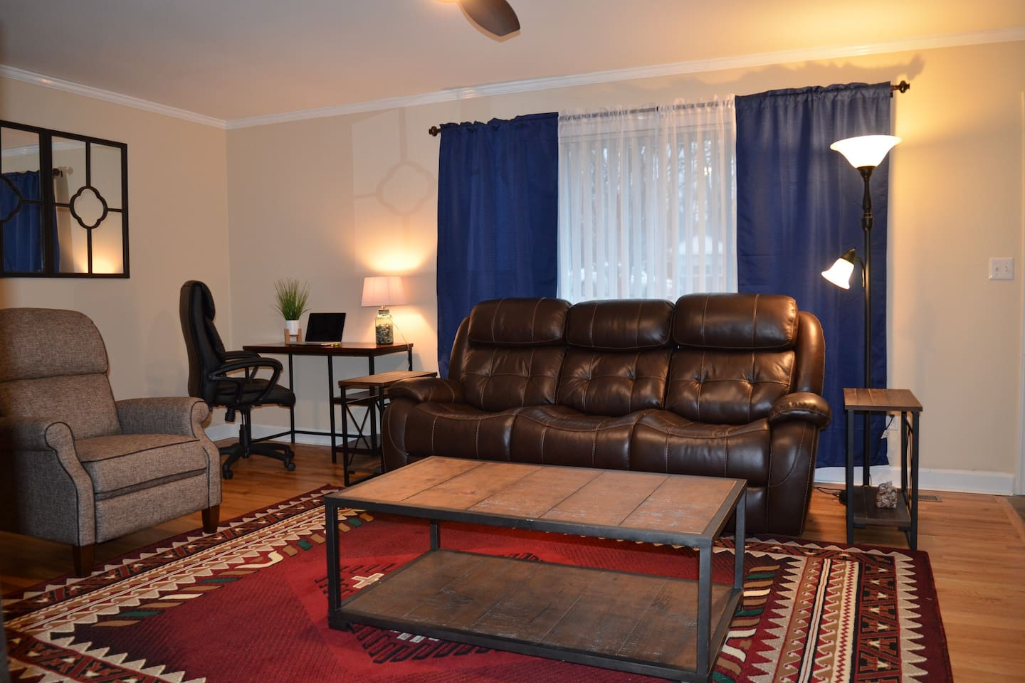 Living room with a ceiling fan (not pictured) and desk work area. Electronic recliners on ends of the sofa, and the arm chair pushes to recline.  We like to rest our legs!