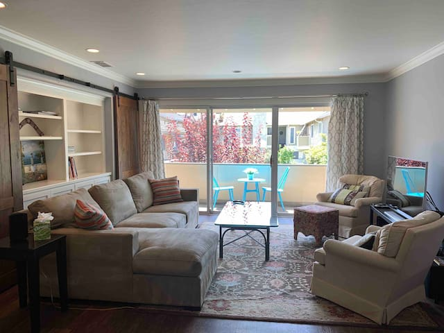 Spacious living room with cable tv and huge glass doors bringing in lots of natural light and cool breeze.