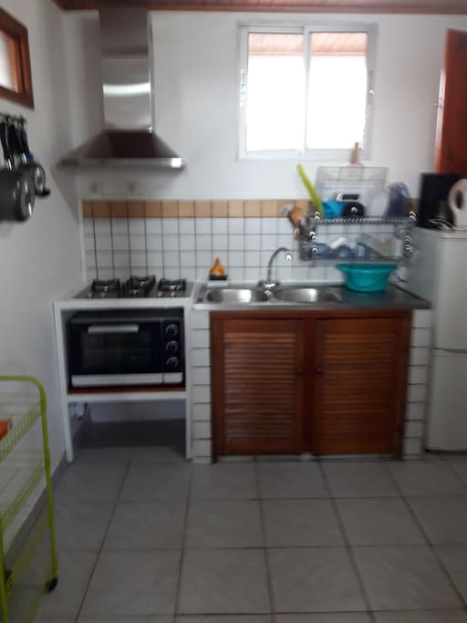 coin cuisine avec refrigérateur ,évier, table de cuisson, cafetière, vaisselles.