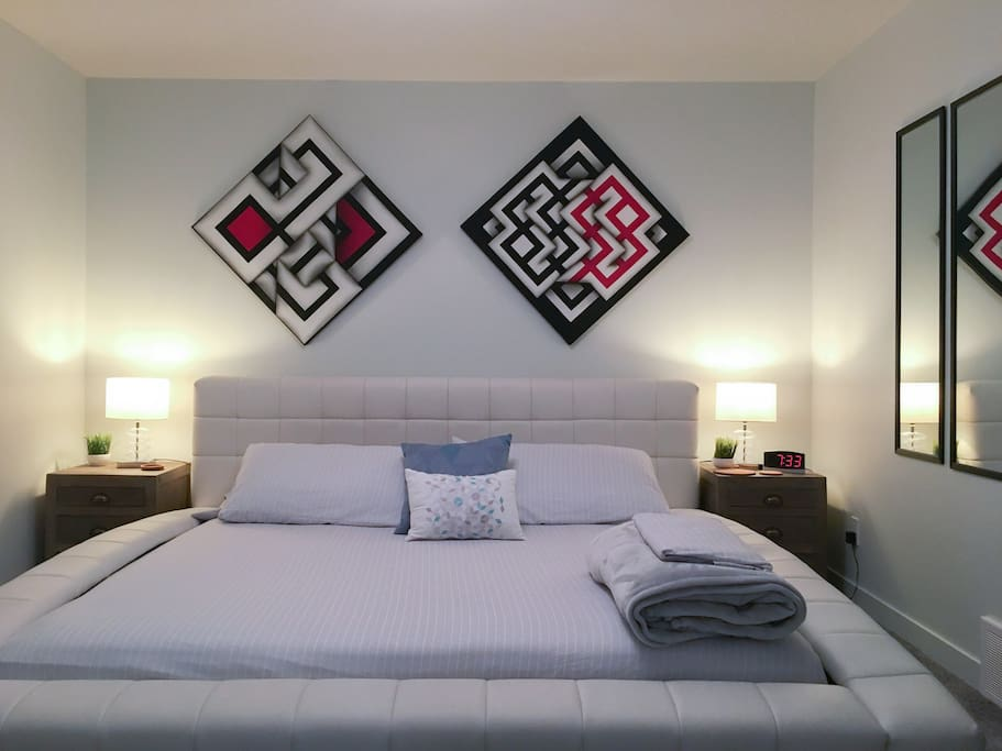 King size platform bed with high end mattress, room decorated with optical art paintings.
