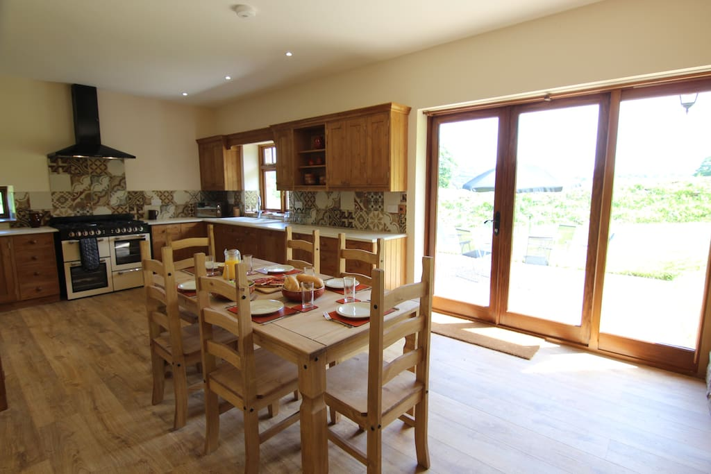 The solid wood kitchen has dishwasher, gas range cooker, fridge/freezer, microwave, seats six with French doors onto the seating area and garden.