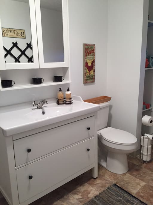 Cottage bathroom with vanity, toilet, tub/shower and open linen closet.