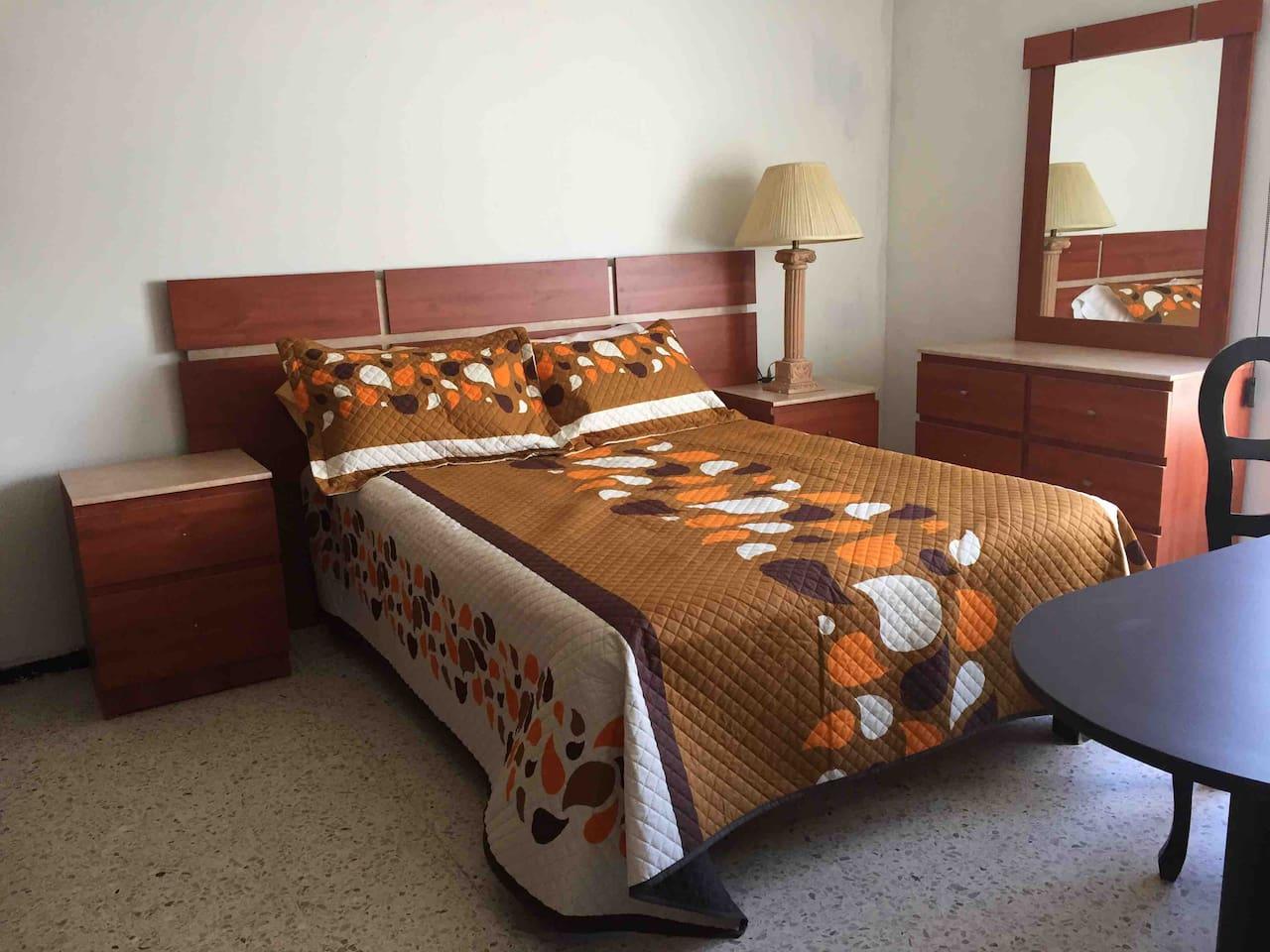 Cómoda Habitación amueblada con una cama matrimonial, tocador, closet, dos sillas y un ventilador de techo para que su estancia sea refrescante en tiempo de calor, baño completo exclusivamente para esta habitación
