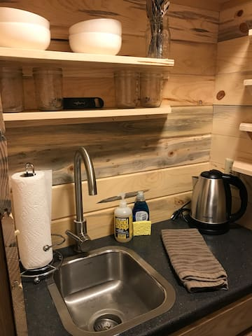 Kitchenette area includes sink, dishes, French press coffee supplies and an electric kettle.