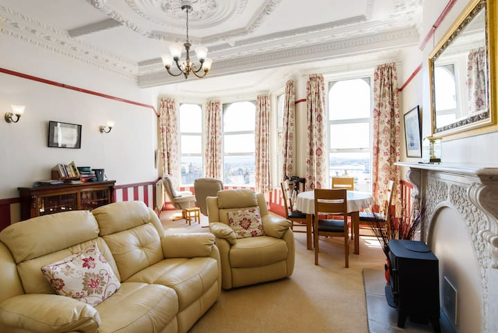 Large living space with bay window with astounding views of the sea, the beach, the pier and the hills beyond