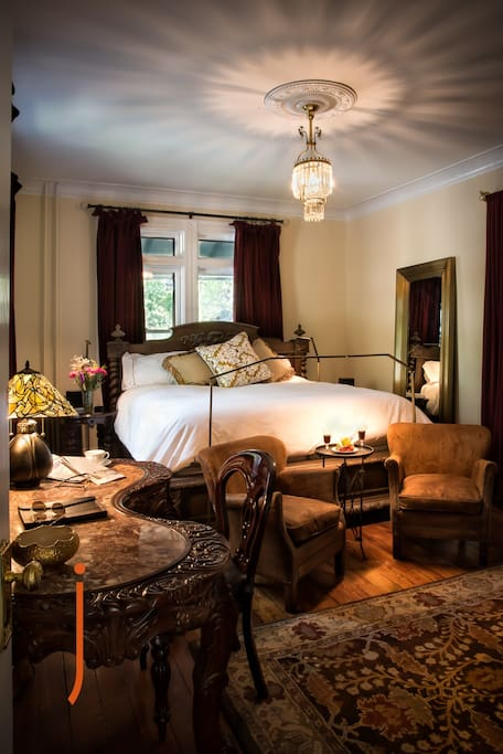 "Elegant king size bed in the Meyer Room at the JL Mott Mansion has subtle touch controlled LED lighting, carved wooden furniture, QLED 55"" surround sound movie system."