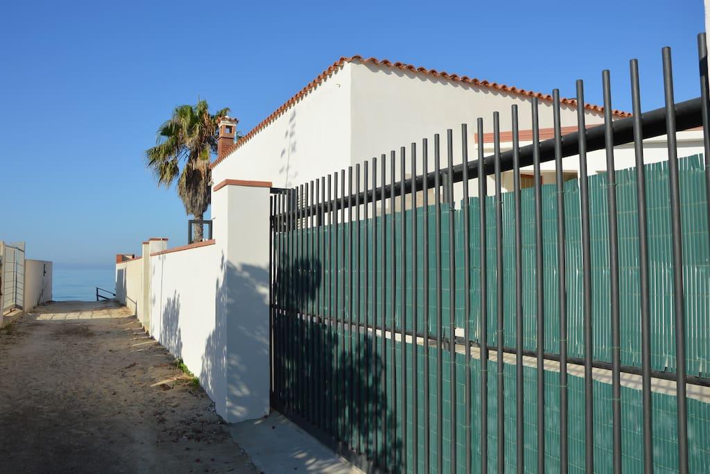 Ingresso di Villa Luna: il cancello, la palma e il mare . La stradina che porta a Villa Luna sul Viale Windsurf.