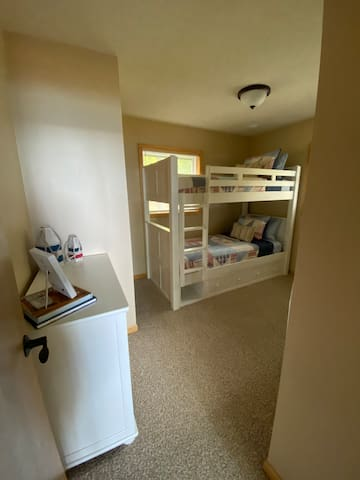 Bunk room located on the lower level includes twin xl bunks, desk, laundry, and full closet.