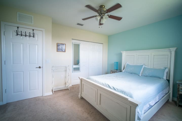 bright queen bedroom with desk, closet and lake view