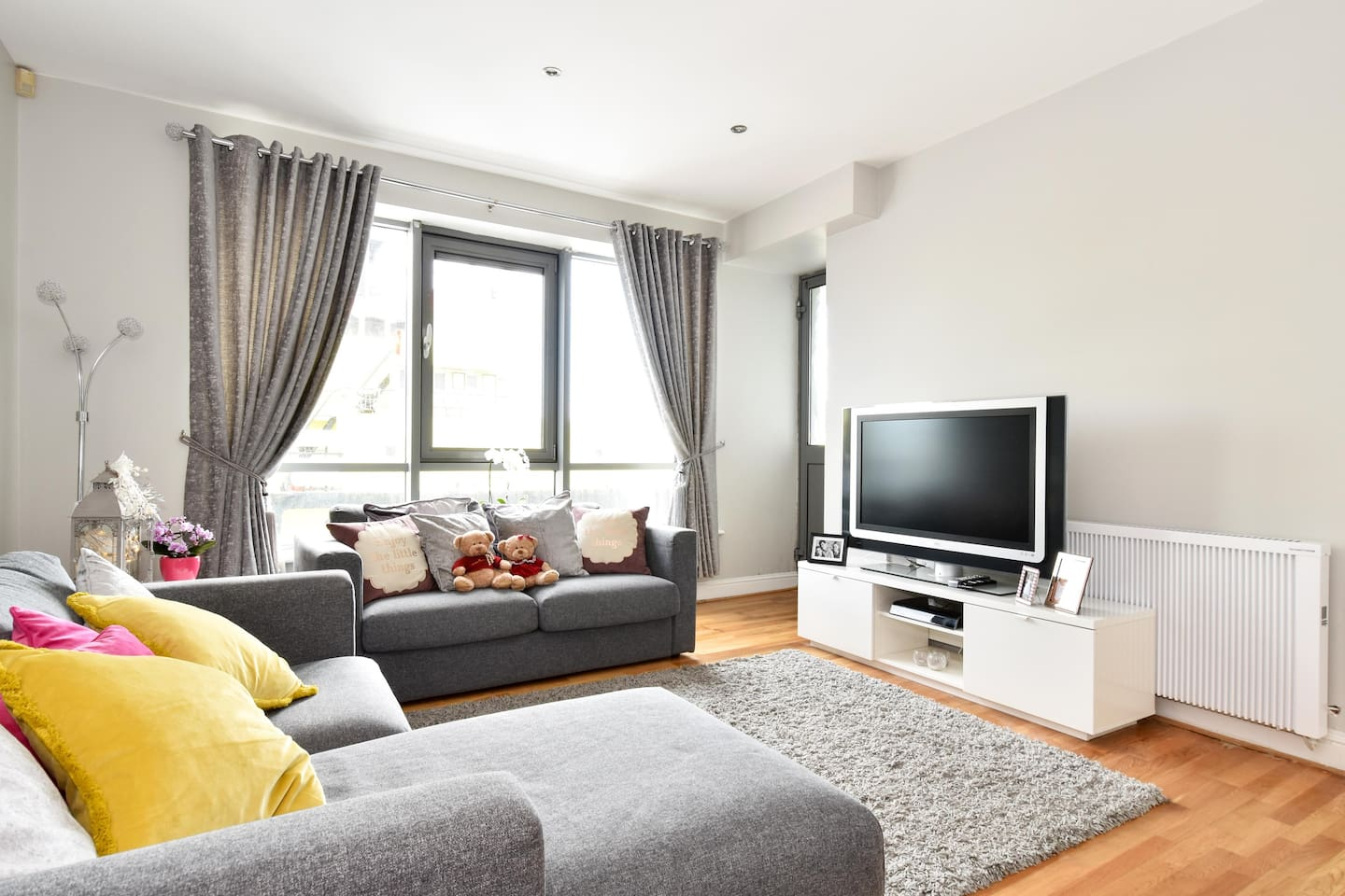 Modern, neutral, spacious living room with large TV, Chromecast, a full selection of digital TV channels, and high-speed WiFi. There's also a terrace through the grey door, overlooking the marina and harbour.