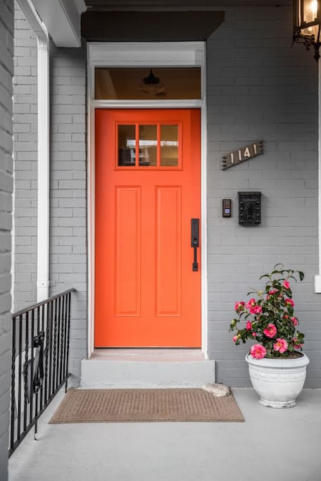 Front door of the row house stands out with its gorgeous orange door. Keyless entry through the basement flat. A key to the front door is provided.