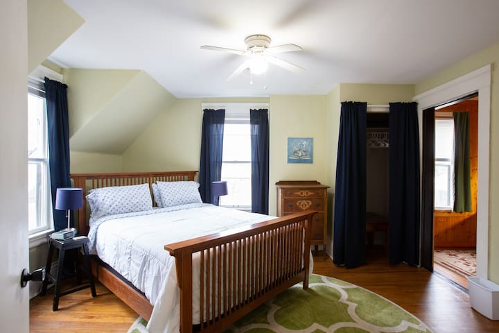 First bedroom with a queen bed, small office and a smart TV.