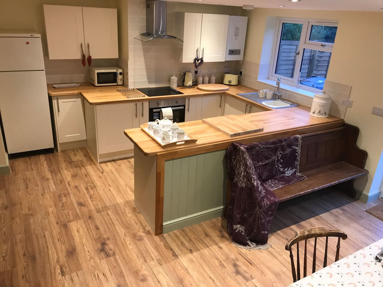 This is the newly installed kitchen combined with a dining area to seat 8 (using an old oak table, chairs & pew). Off of here is a utility area & hidden downstairs toilet!!