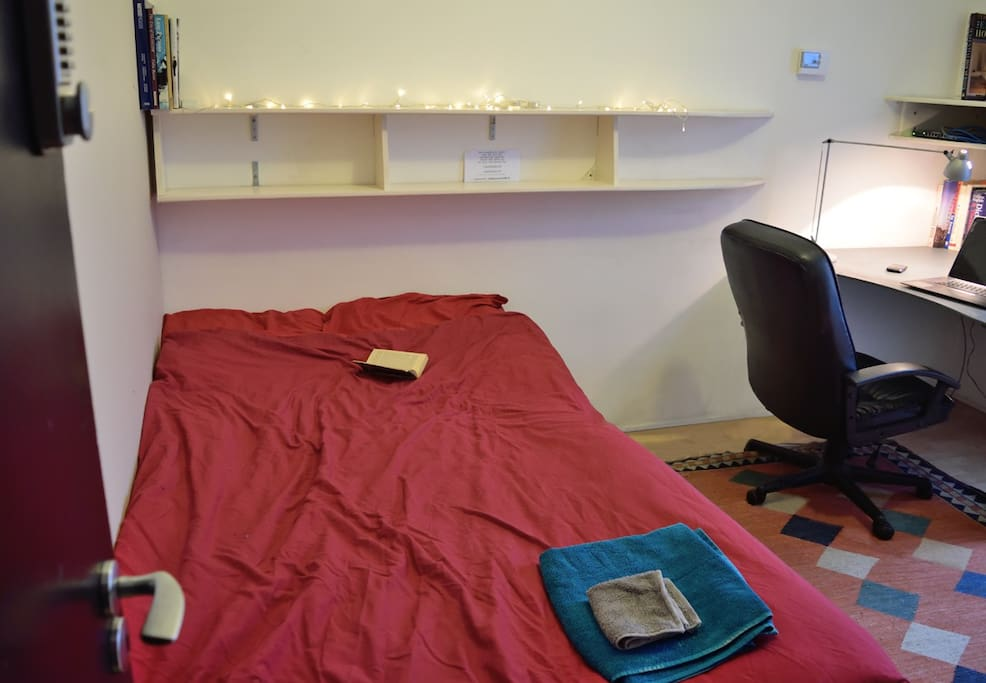 shows the bed, shelving, armchair, desk and door with digital lock.