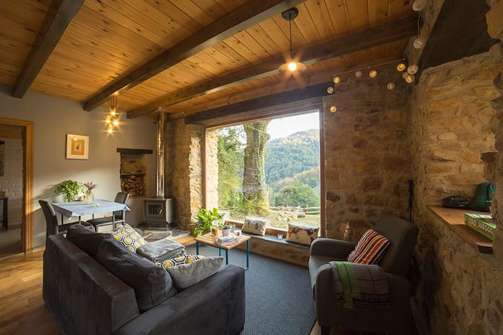 Modern meets rustic in cozy living room with breathtaking views from feature window...living room equiped with telescope, board games, bluetooth speaker, various books, fireplace and much more...