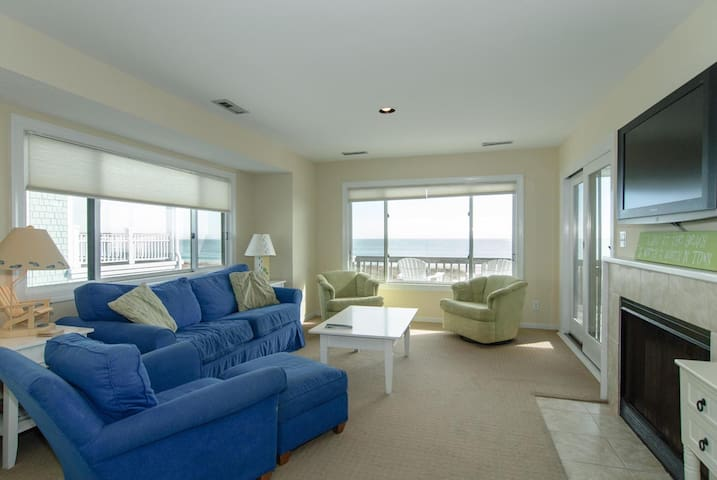 Living room with sleeper sofa and access to oceanfront deck area.