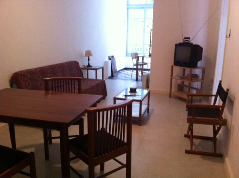 Sala de estar com mesa, televisão e sofá // Lounge with table, tv and sofa.
