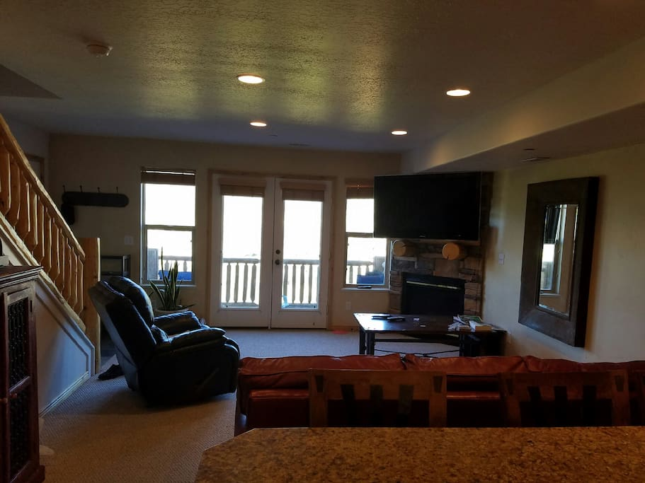 "Living room with 55"" HDTV, gas fireplace, and doors to one of the balconies"