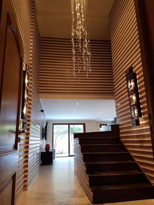Entrée avec belle hauteur sous plafond (5m) et escalier 3/4 tournant vers chambres.