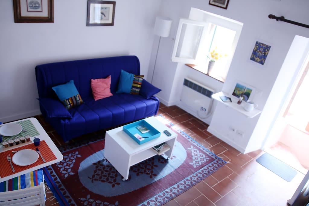 ingresso su salotto luminoso con comodo divano letto.