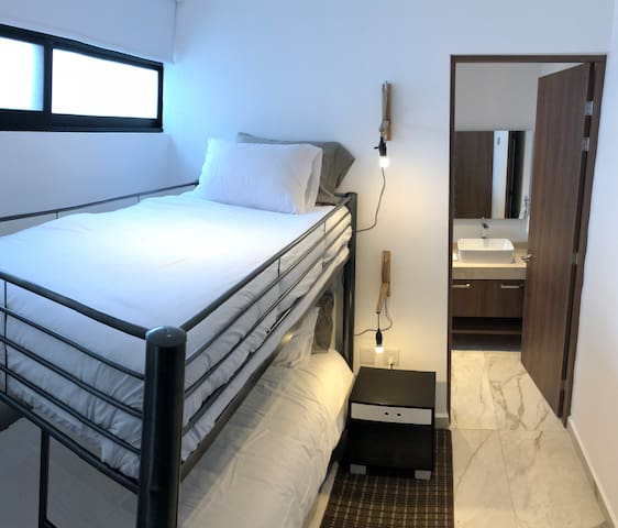 Second bedroom in lower floor has a bunk bed, closet and en suite bathroom