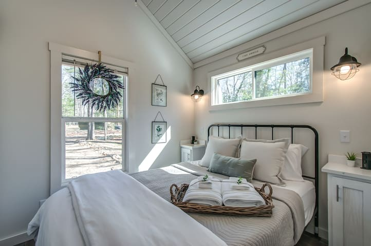 Master Bedroom with TONS of natural light AND reading lamps on both sides. Also has pop-up receptacles on each bed-side table for charging your devices.