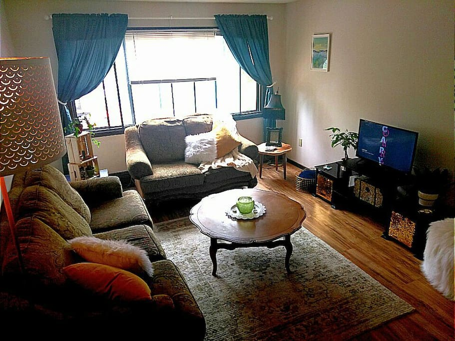 Enjoy lounging on our super comfy couch, love seat, and footstools in this spacious living room. Bright and warm mornings and days with eastern facing windows!