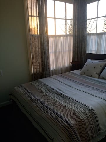 Queen size bed with beautiful windows lots of natural light.
