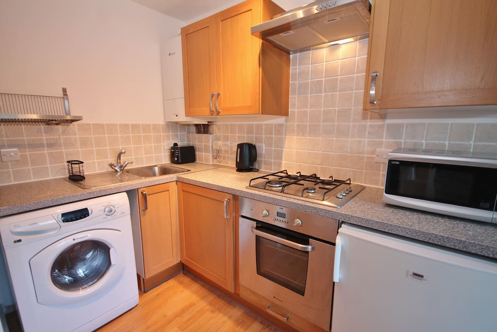 Kitchen with washer/dryer, cooker, fridge and microwave